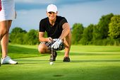 image of ball cap  - Young golf player on course putting - JPG