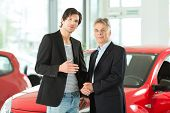 Mature single man with red auto in light car dealership with a male customer, a young man, he is obv