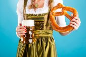 Young woman in traditional Bavarian clothes - dirndl or tracht with a beer stein and beer and pretze