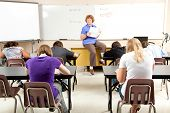 Teacher at the head of the class, teaching algebra to high school students.