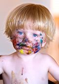 Young Boy With Face Covered In Colourful Paint