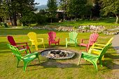 outdoor fireplace with three colorful chairs