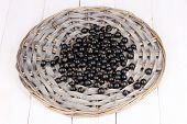 Black currant on wicker mat on wooden background