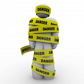 A person or man wrapped in yellow tape marked Danger, illustrating a warning, caution, hazard, crisi