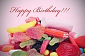 a pile of candies with the sentence happy birthday written in red