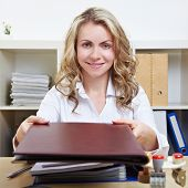 Smiling blonde woman in office offering her application material