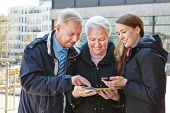 Family on city trip navigating with map and smartphone app