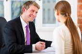 Young lawyer, insurance agent or attorney working in his office and has a consultation with a female