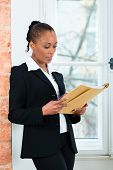 Young female lawyer or businesswoman standing at a window in office reading a file or dossier