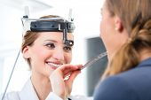 Médico - jovem médico feminino ou otorrinolaringologista - com um paciente em sua prática, examinando a garganta