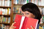 Schüler - junge asiatische Frau oder ein Mädchen lernen in der Bibliothek und lesen, She versteckt hinter einem Buch