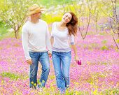 Beautiful happy couple enjoying spring nature, laughing and having fun outdoors, walking on purple f