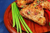 roast meat : chicken legs garnished with green onion pens and peppers on wooden plate over blue wooden background