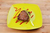 meat savory : grilled beef fillet mignon on green plate with chives and ketchup over wooden table
