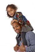 Afro father giving little daughter a shoulder ride, both smiling.