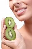 stock photo of fat lip  - Closeup lips of smiling young healthy woman with kiwifruit in hand - JPG