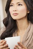 A beautiful young Chinese Asian Oriental woman drinking tea or coffee from a white cup
