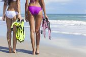 Rear view of two beautiful young women in bikinis with snorkel, mask & flippers on a deserted beach with blue sky