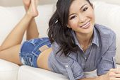 A beautiful young Chinese Asian Oriental woman or girl with a wonderful toothy smile laying down on a sofa wearing denim shorts