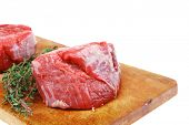 red raw fillet chops : two fresh beef meat chops with small thyme twig on wooden plate . isolated ov