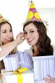 Two beautiful caucasian girls celebrating birthday wearing holiday hats