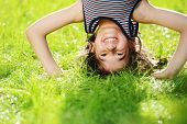 stock photo of barefoot  - Portraits of happy kids playing upside down outdoors in summer park - JPG