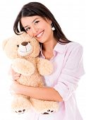 Sweet woman hugging a teddy bear and smiling - isolated over white
