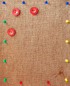 Burlap Background Decorated With Pins, Buttons And Needle