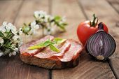 Sandwich with salami, red onion, tomato  and cherry flowers