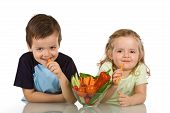 stock photo of healthy eating girl  - Happy kids with a bowl of vegetables smiling and eating carrot  - JPG
