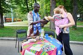 MOSCOW - AUGUST 17: Black man shows drum caucasian baby and her mother at International Festival of