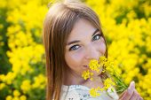 Cheerful Girl Smelling Yellow Wildflower