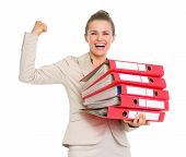 Smiling Business Woman Holding Stack Of Folders And Showing Biceps