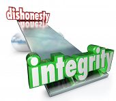 The words Integrity and Dishonesty on scale, balance or see-saw to illustrate the difference and com