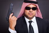 arab hit man holding gun on black background