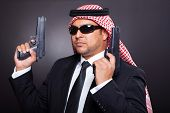 young middle eastern hitman posing with guns over black background