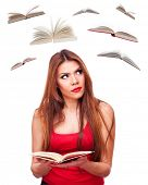 Beautiful brunette holding book in the hands and looking flying books around, isolated on white