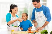 stock photo of apron  - little girl tasting tomato while her parents cooking in kitchen at home - JPG