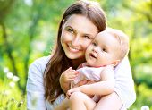 Beautiful Mother And Baby outdoors. Nature. Beauty Mum and her Child playing in Park together. Outdoor Portrait of happy family. Mom and Baby portrait