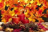 stock photo of auburn  - Candles in nice and beautiful colorful autumn leaves - JPG