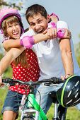 Teenage girl embracing her dad on the bike