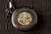 pic of wind up clock  - Old watch machine on dark background  - JPG