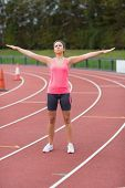 Full length of a toned young woman doing stretching exercise on the running track