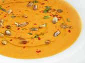 Hot healthy vegetarian pampkin cream soup with pampkin seeds in a round palate