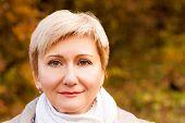 Portrait of Senior Woman on Autumn Background