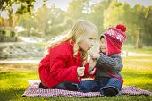 Little Girl with Her Baby Brother Wearing Winter Coats and Hats Sharing a Lollipop Outdoors at the P