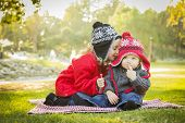 Little Girl Whispers A Secret to Her Baby Brother Wearing Winter Coats and Hats Sitting Outdoors at