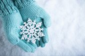 Female hands in light teal knitted mittens with sparkling wonderful snowflake on a white snow backgr