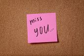 stock photo of miss you  - pink reminder sticky note on cork board miss you phrase - JPG
