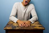picture of table manners  - Tired Man is sitting at a desk and Yawning - JPG